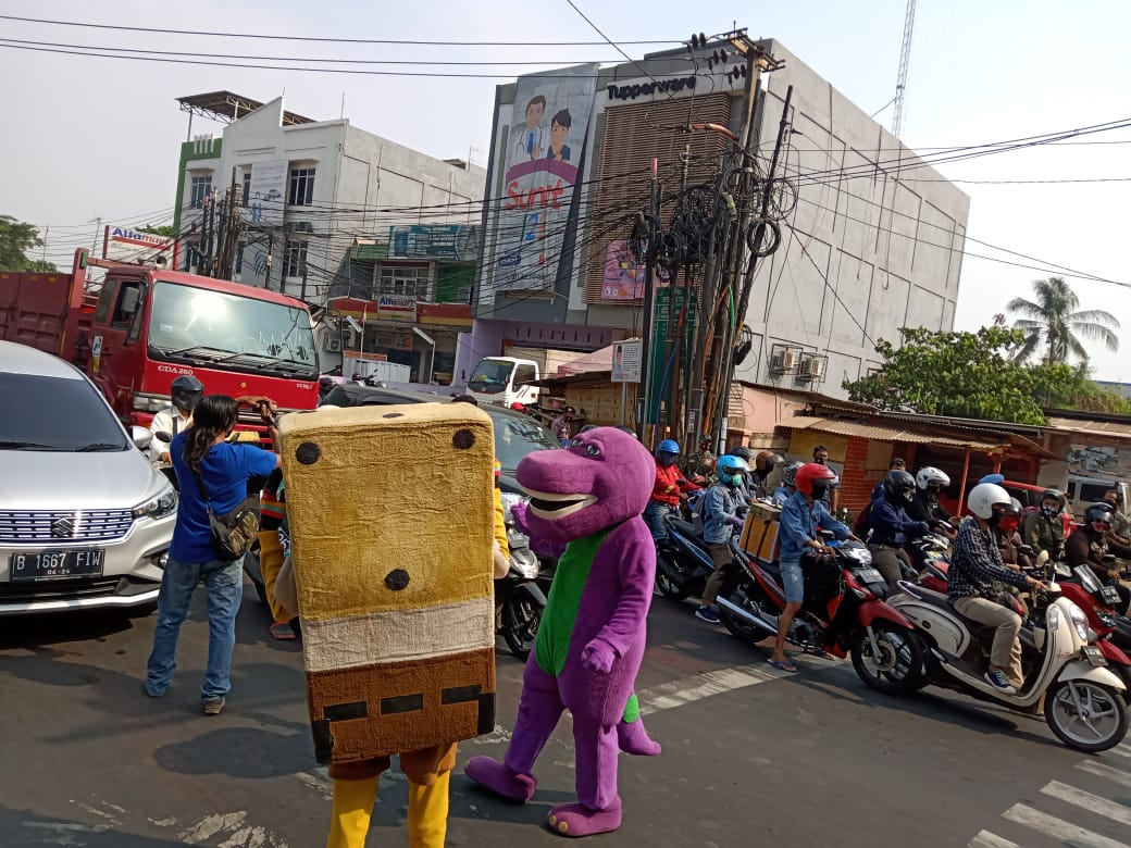 """Sementara itu, di Kolong Tol Simpang Cibitung, polisi juga berkampanye bahaya Covid-19, Polsek Cikarang Barat melibatkan Spongebob dan Barney dengan membagikan 1.500 Masker  Polisi juga membentangkan spanduk berisi pesan-pesan protokol kesehatan. Pemilihan tempat di Simpang Cibitung lantaran merupakan tempat masyarakat berlalu lalang untuk beraktivitas.   Sewaktu lampu menyala merah, terlihat kostum Spongebob dan Barney, menghampiri para pengendara bersama polisi. Bagi-bagi masker di sana juga dilantunkan dengan alat musik angklung.  """"Insya Allah ini efektif dan akan kami lakukan secara simultan. Kita terus berusaha dan tidak menyerah dalam pengendalian covid-19,"""" kata Kapolsek Cikarang Barat, AKP Akta Wijaya."""